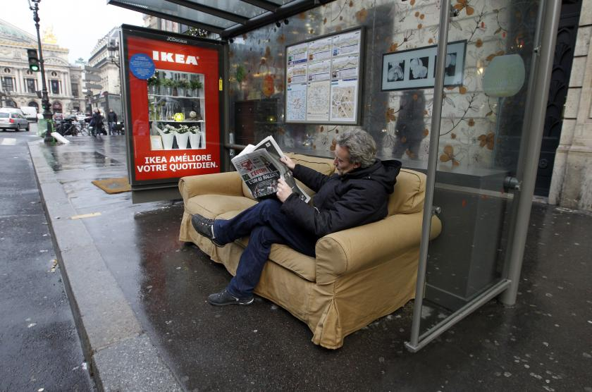 Buiten reclame campagne man leest krant in huiskamer bushalte